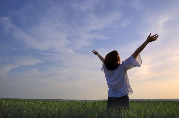Mujer adorando a Dios en el campo